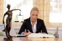 female attorney working at her desk with Lady Justice statue in the foreground